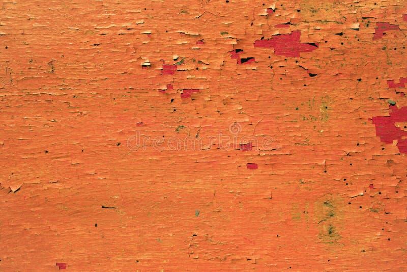 Textura de una pintura anaranjada de la peladura en vieja superficie de madera fotos de archivo