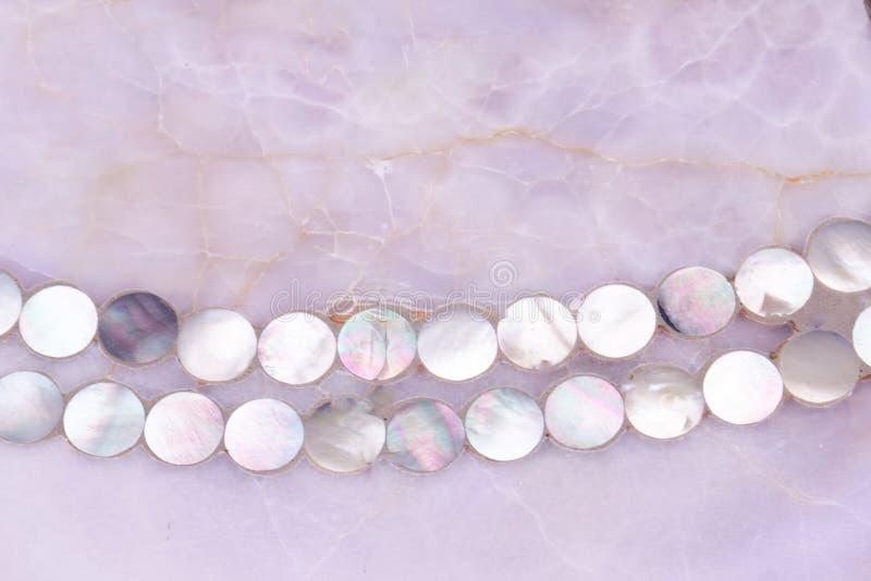 Textura del cuarzo de Rose con el pequeño ornamento del collar de las cáscaras de la perla de la madre fotografía de archivo libre de regalías