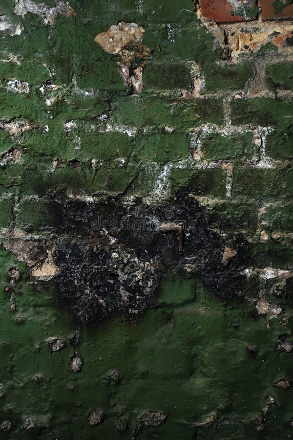Textura del fondo de la pared de ladrillo vieja con la pintura verde lamentable y el yeso agrietado fotos de archivo libres de regalías