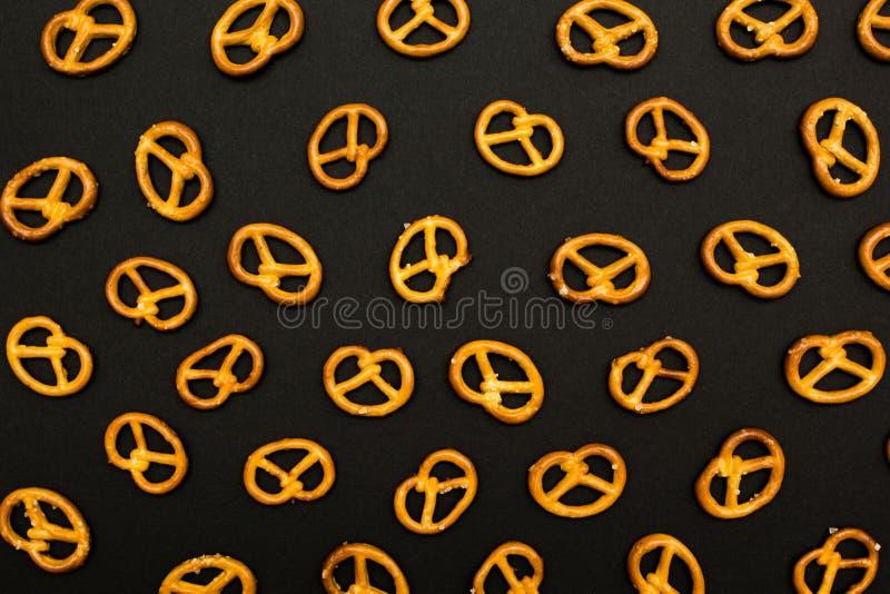 Textura del fondo de mini pretzeles sabrosos salados en la forma tradicional del nudo colocado en el fondo negro foto de archivo