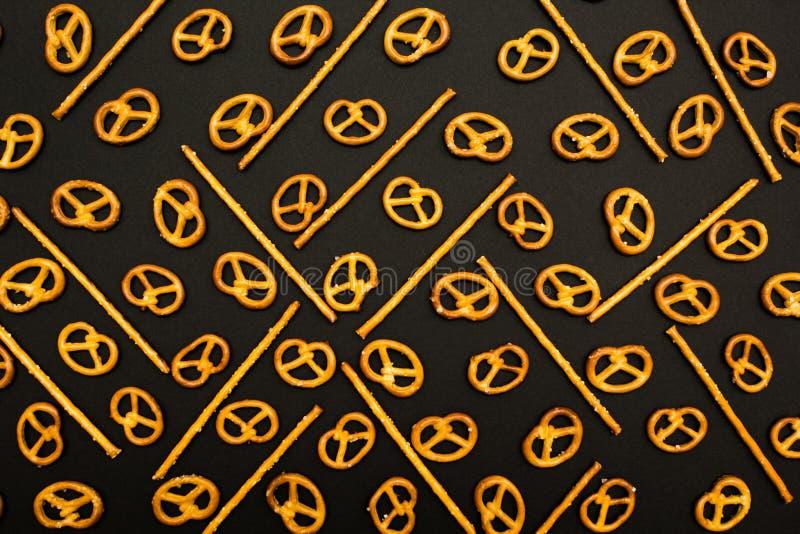 Textura del fondo de pretzeles salados salados y de mini palillos en la forma tradicional del montaje de bisagra en un fondo negr foto de archivo libre de regalías