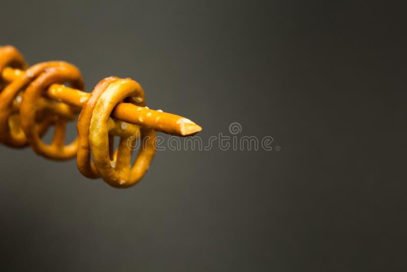 Textura del fondo de pretzeles salados salados y de mini palillos en la forma tradicional del montaje de bisagra en un fondo negr fotos de archivo