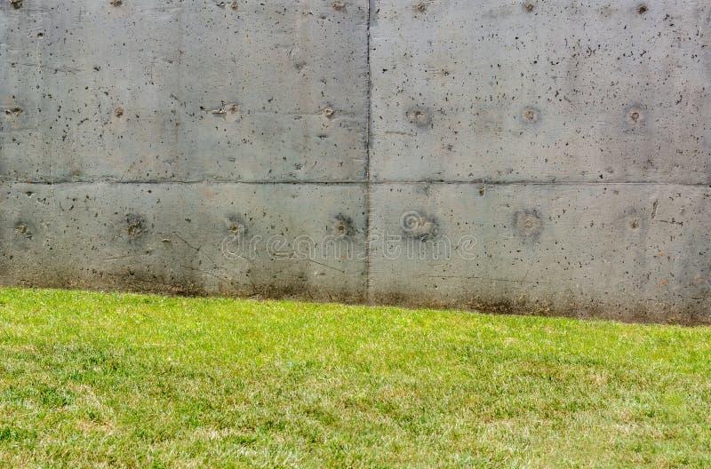 Textura del muro de cemento gris con pequeñas depresiones e hierba imagen de archivo