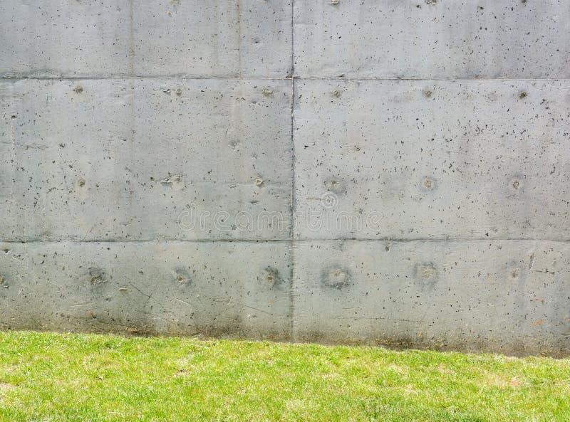 Textura del muro de cemento gris con pequeñas depresiones e hierba foto de archivo libre de regalías