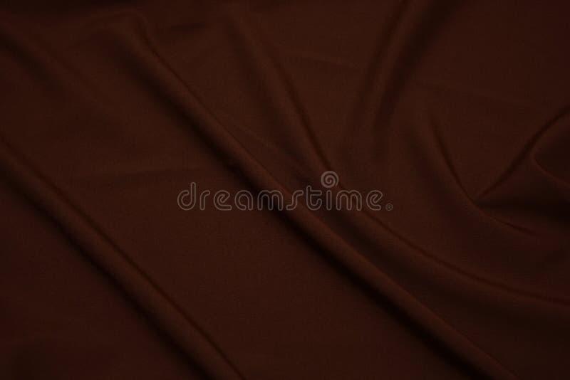 Textura del primer marrón oscuro de la tela Foto oscura Hilos del plexo Industria de la confección abstraiga el fondo Ondas de la fotos de archivo