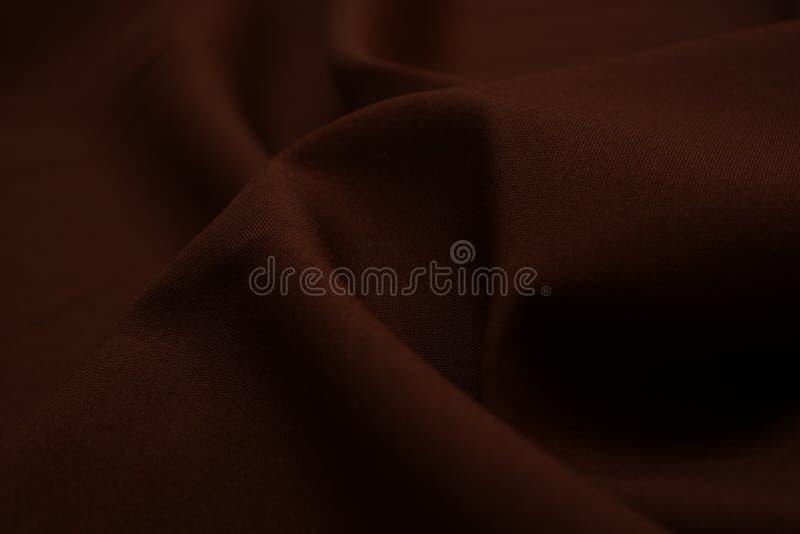 Textura del primer marrón oscuro de la tela Foto oscura Hilos del plexo Industria de la confección abstraiga el fondo Ondas de la imagen de archivo libre de regalías