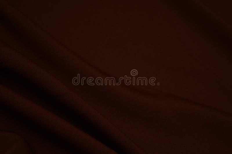 Textura del primer marrón oscuro de la tela Hilos del plexo Industria de la confección abstraiga el fondo Ondas de la materia tex foto de archivo