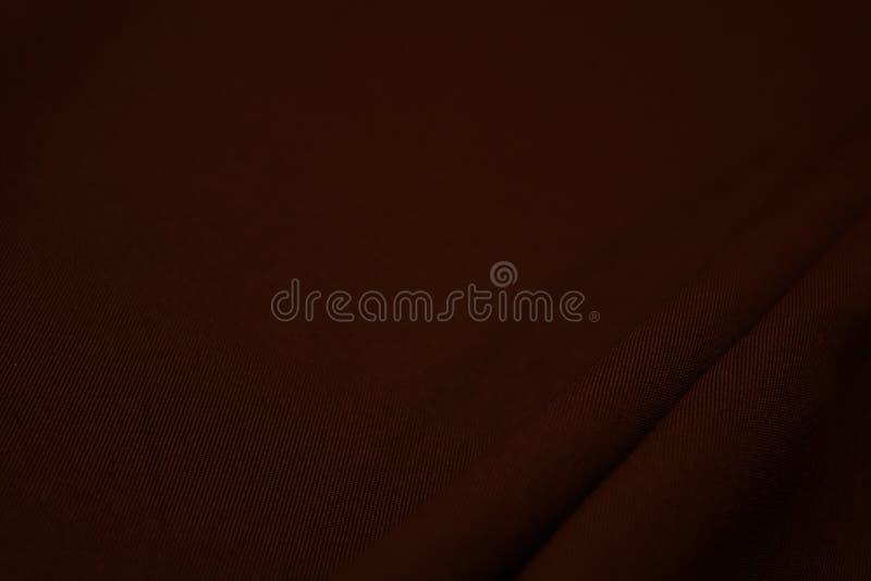 Textura del primer marrón oscuro de la tela Hilos del plexo Industria de la confección abstraiga el fondo Ondas de la materia tex imagenes de archivo