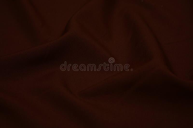 Textura del primer marrón oscuro de la tela Hilos del plexo Industria de la confección abstraiga el fondo Ondas de la materia tex imágenes de archivo libres de regalías