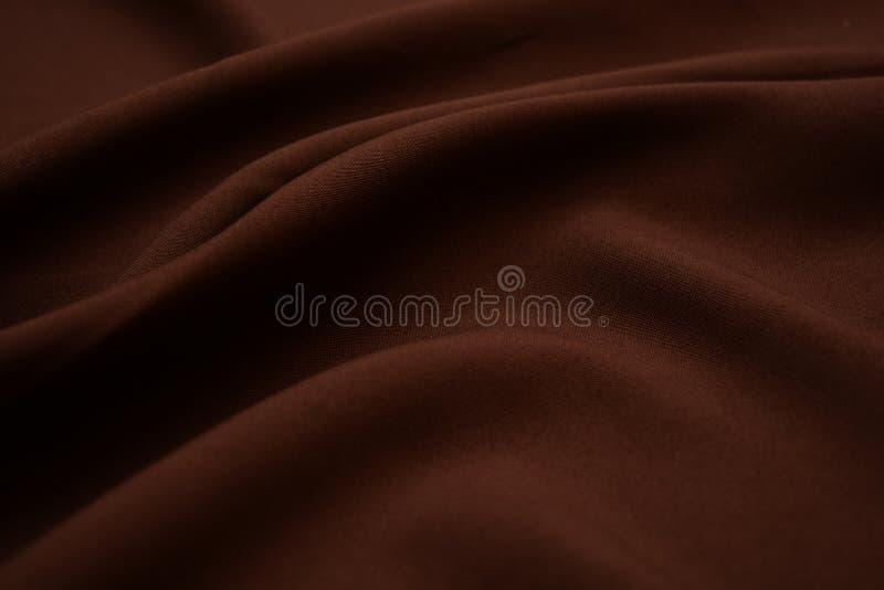 Textura del primer marrón oscuro de la tela Hilos del plexo Industria de la confección abstraiga el fondo Ondas de la materia tex fotografía de archivo libre de regalías