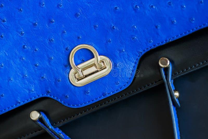 Textura do close-up da bolsa azul da cor da forma vívida, couro genuíno com gravado sob a pele da avestruz, fechamento do ouro foto de stock