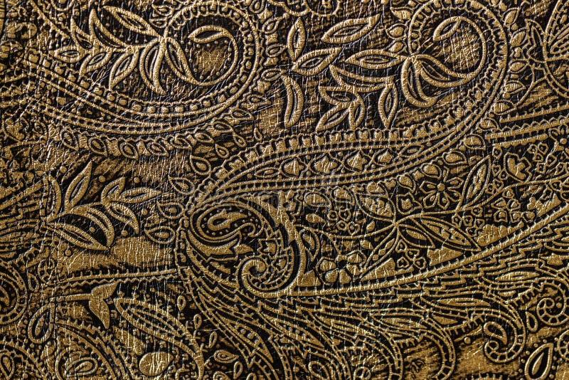 Textura do close-up de couro genuíno marrom dourado, com teste padrão da tendência, o papel de parede ou projeto floral gravado d fotografia de stock