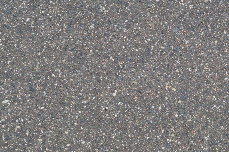 A textura do fundo da estrada asfaltada cinzenta do preto da pedra com seixos pequenos imagens de stock