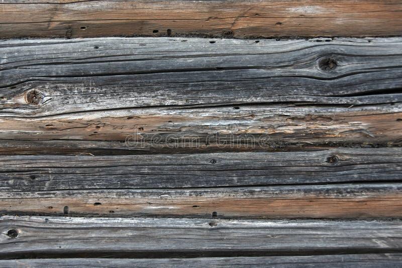 Textura do fundo de uma parede de logs e de placas de madeira idosos fotos de stock royalty free