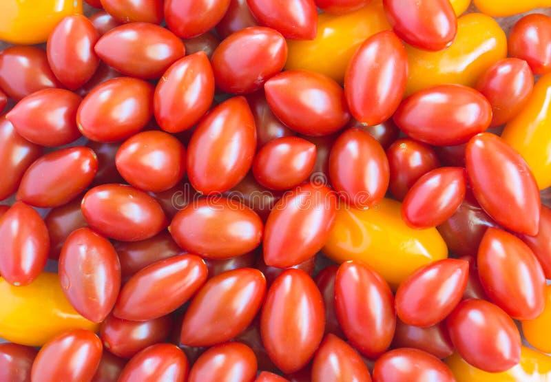 Textura do fundo - desordem de tomates vermelhos e alaranjados da uva imagem de stock
