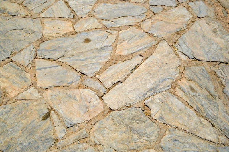 A textura do marrom velho, antigo grosseiro cinzelado, pedras desiguais com pontos colocou no assoalho no bristchatku O fundo fotos de stock royalty free