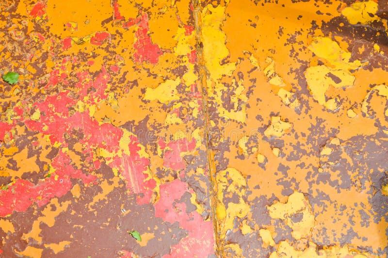 A textura do metal do ferro pintou a pintura de descascamento amarela vermelha colorido de velho golpeado riscado rachou a folha  imagem de stock
