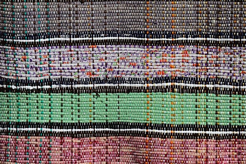 A textura do tapete feito a mão feita no mão-tear com quatro cores diferentes dividiu-se com linhas verticais gêmeas imagem de stock