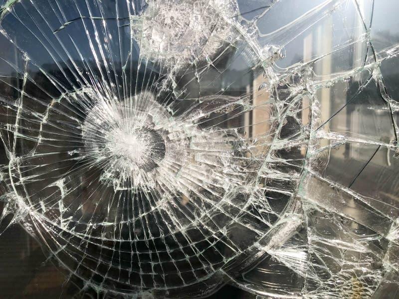 A textura do vidro afiado quebrado frágil grosso rachado quebrado, triplex com fragmentos pequenos brilhantes O fundo imagem de stock royalty free