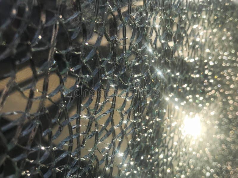 A textura do vidro afiado quebrado fr?gil grosso rachado quebrado, triplex com fragmentos pequenos brilhantes O fundo fotos de stock