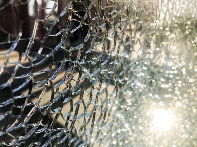 A textura do vidro afiado quebrado fr?gil grosso rachado quebrado, triplex com fragmentos pequenos brilhantes O fundo imagens de stock