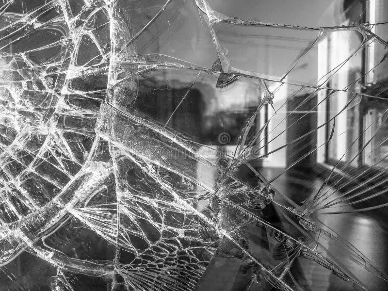 A textura do vidro afiado quebrado fr?gil grosso rachado quebrado, triplex com fragmentos pequenos brilhantes O fundo foto de stock
