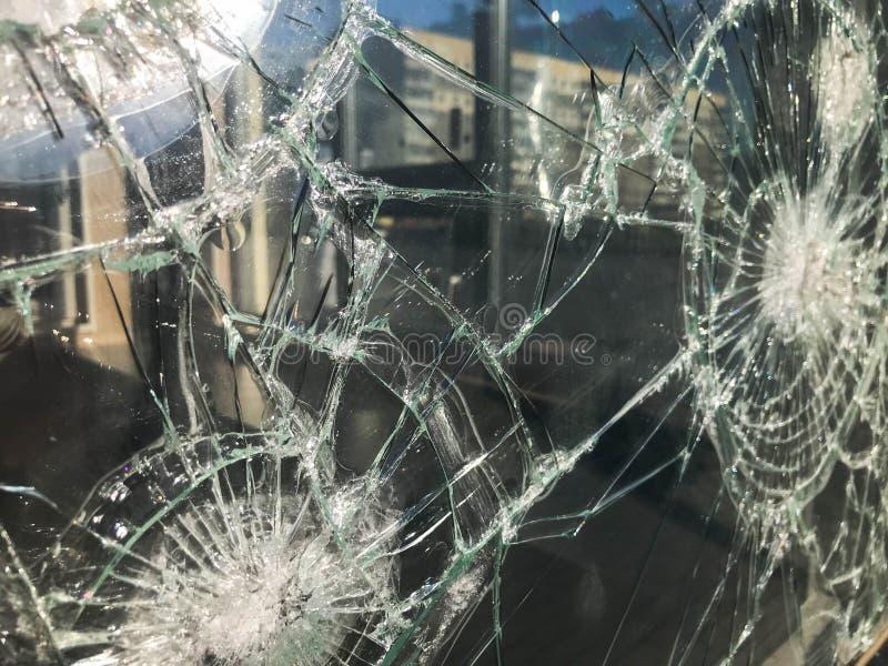 A textura do vidro afiado quebrado fr?gil grosso rachado quebrado, triplex com fragmentos pequenos brilhantes O fundo imagem de stock