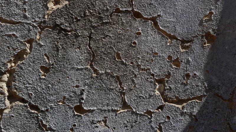 Textura dramática de la pared gris oscuro del cemento con las grietas profundas onduladas foto de archivo