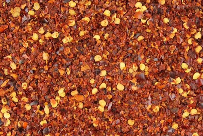 Textura esmagada do fundo do alimento do close up dos flocos de pimenta vermelha foto de stock royalty free