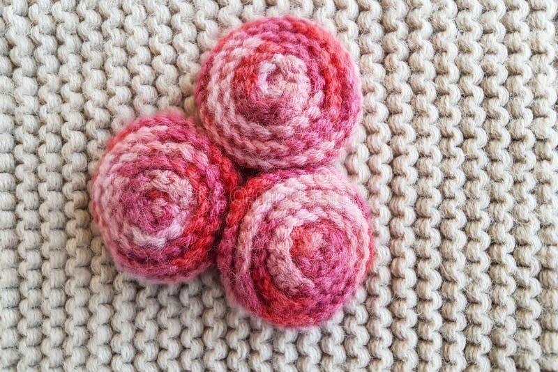 A textura feita malha bege da tela com o ornamento vermelho em bolas vermelhas/aumentou flores imagem de stock
