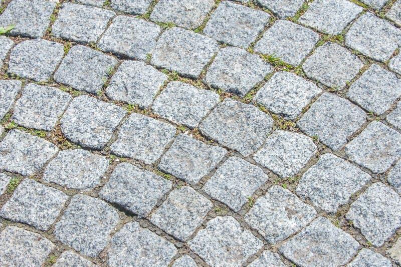 Textura, fondo El pavimento de la piedra del granito Roadwa pavimentado imagenes de archivo