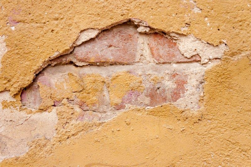 Textura gasto rústica áspera do fundo da parede velha com o tijolo de vermelho rachado amarelo do emplastro e do vintage fotos de stock royalty free