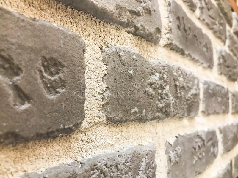 Textura hermosa de una pared de piedra decorativa en ángulo de construir el ladrillo texturizado gris del alivio, piedra del yeso imagen de archivo