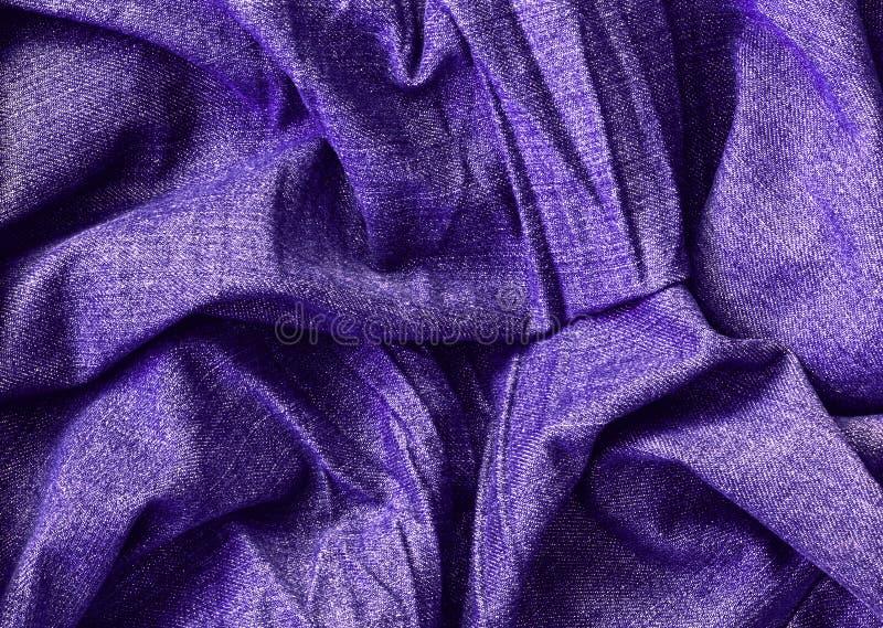 Textura macra de los vaqueros púrpuras ultravioletas, fondo de la ropa con las arrugas fotos de archivo libres de regalías