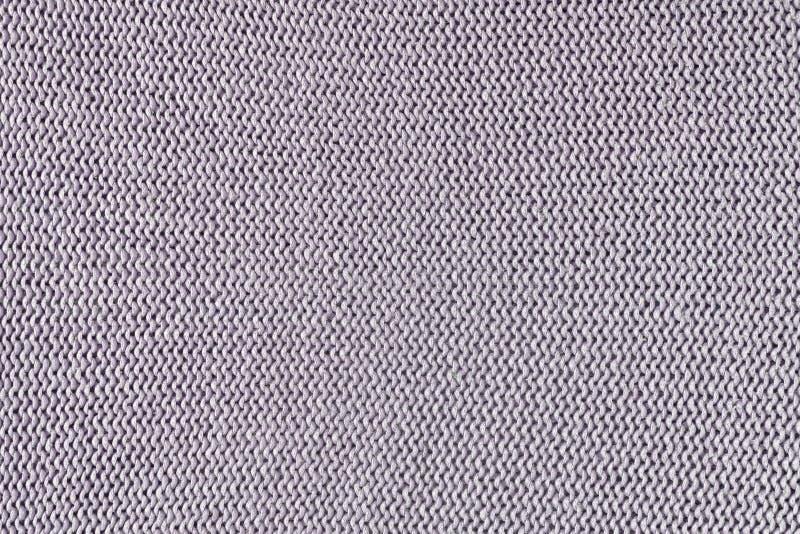 Textura monocromática de hacer punto Fondo hermoso con los lazos La ropa hecha punto es púrpura pálida imagenes de archivo