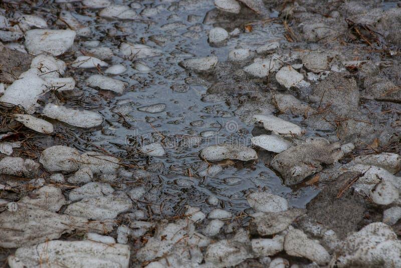 Textura natural de pedazos de hielo gris y de agua fangosa en un charco fotografía de archivo