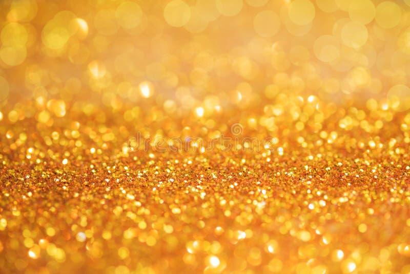A textura ou o brilho claro do bokeh do ouro iluminam o backgrou festivo do ouro fotos de stock royalty free