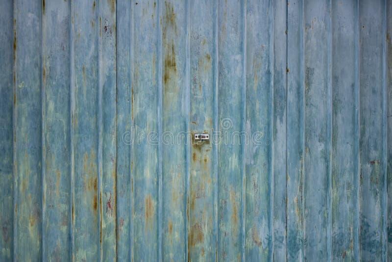 Textura oxidada acanalada de las puertas del garaje del metal con la cerradura en el centro imagen de archivo