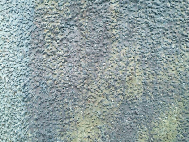 Textura pequena da parede de pedra e fundo azul foto de stock
