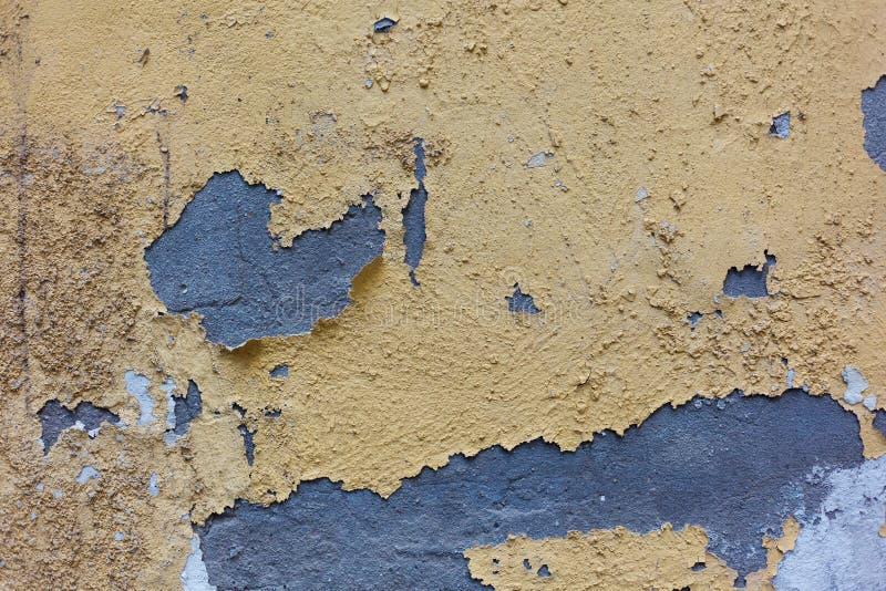 Textura pintada resistida velha do fundo da parede Parede descascada suja amarela do emplastro com queda fora flocos da pintura fotografia de stock royalty free