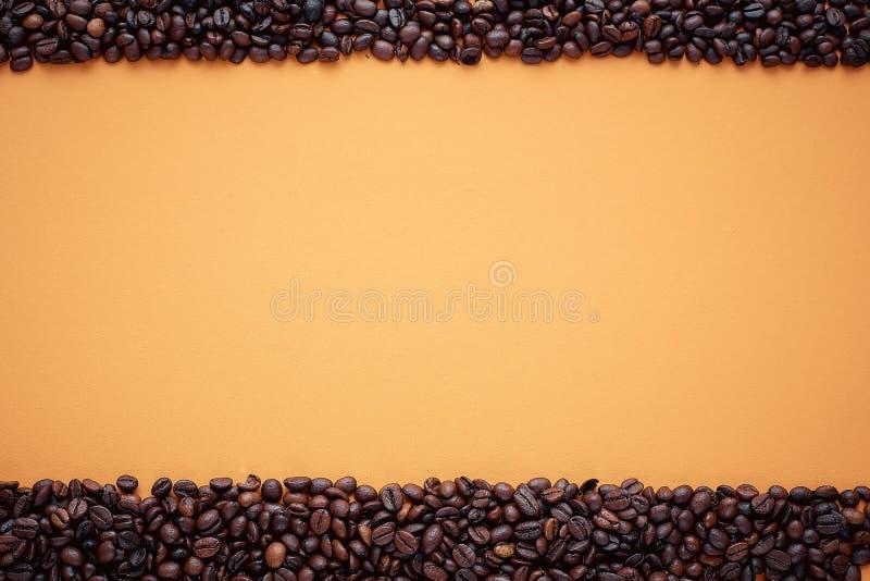 Textura, quadro do feijão de café no fundo alaranjado, espaço para o texto imagens de stock
