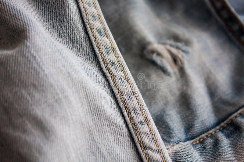 Textura rasgada calças de brim da sarja de Nimes fotografia de stock