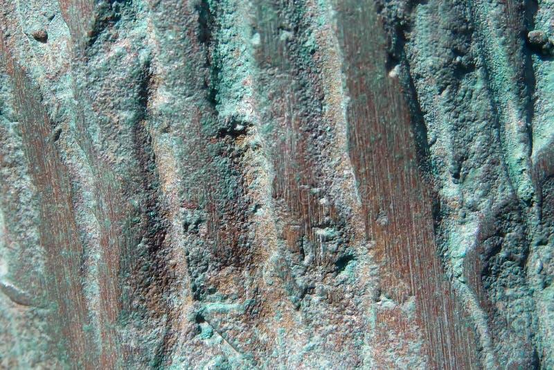 Textural bakgrund av en kopparyttersida med gröna oxiderade delar arkivbild