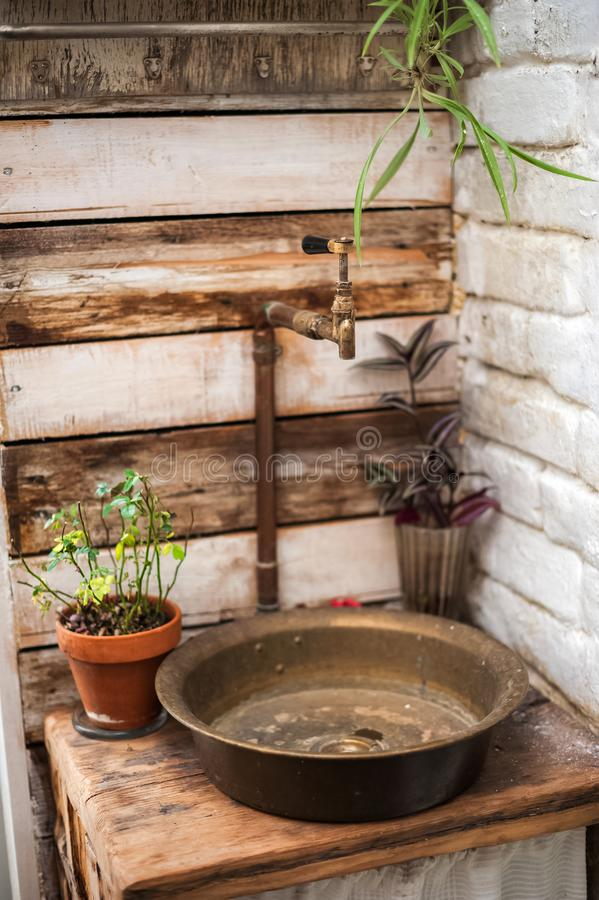 Textural old vintage washbasin in rustic style. Potted flowers in a greenhouse closeup and copy space. Textural old vintage washbasin in rustic style. Potted stock photography