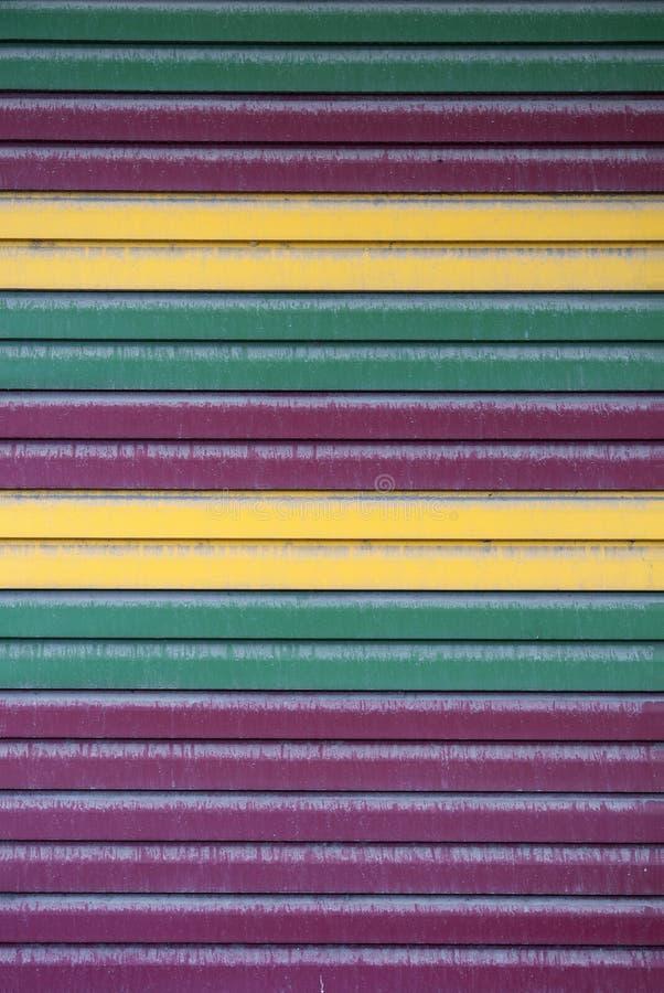 Texturas do fundo do metal pintado Listras coloridas do ferro carmesim, verde e amarelo sujo fotografia de stock royalty free