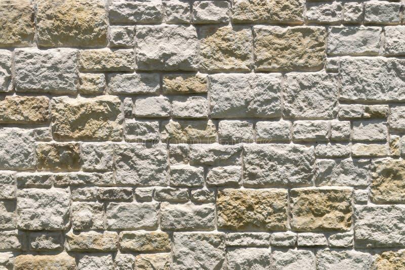 Texturas e testes padrões desiguais de uma parede de tijolo de pedra fotos de stock