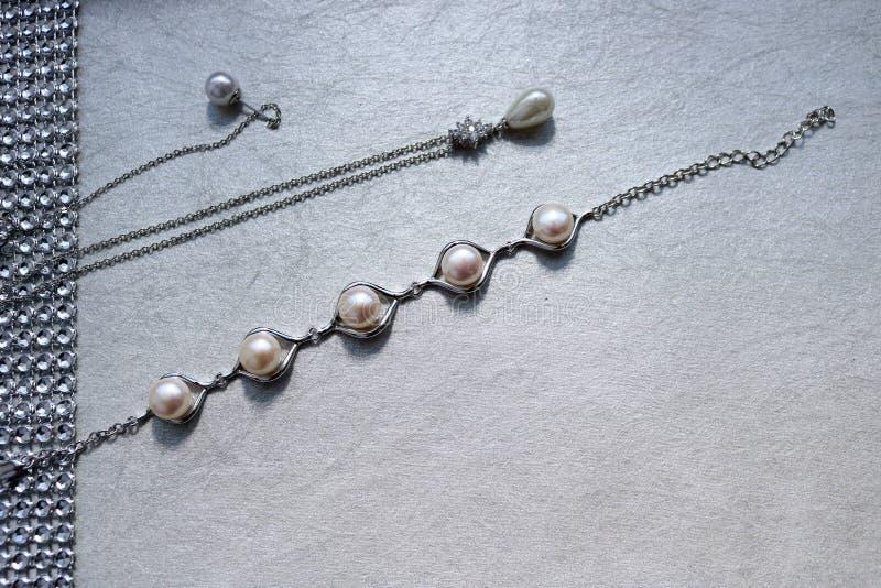 Texture avec des bijoux de perle, perles, chaînes argentées, cristaux des pierres précieuses, diamants, diamants sur un fond gris images libres de droits