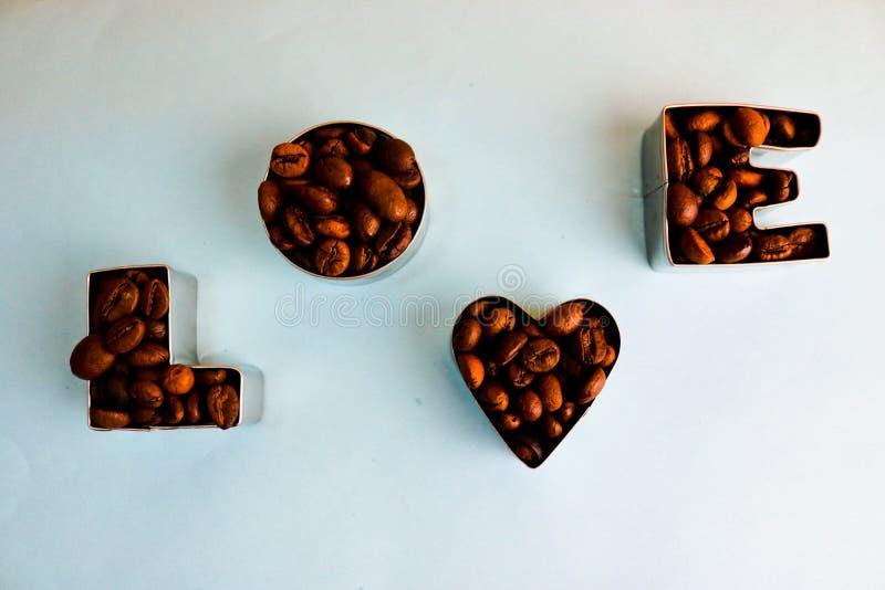 Texture avec l'amour de mot pour l'inscription du jour de valentine faite à partir du fond aromatique brun choisi de grains de ca photographie stock