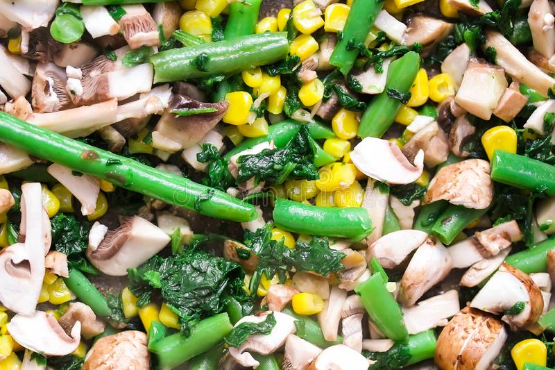 Texture and background of cut vegetables on a pan. Corn, spinach, asparagus, mushrooms close up royalty free stock images