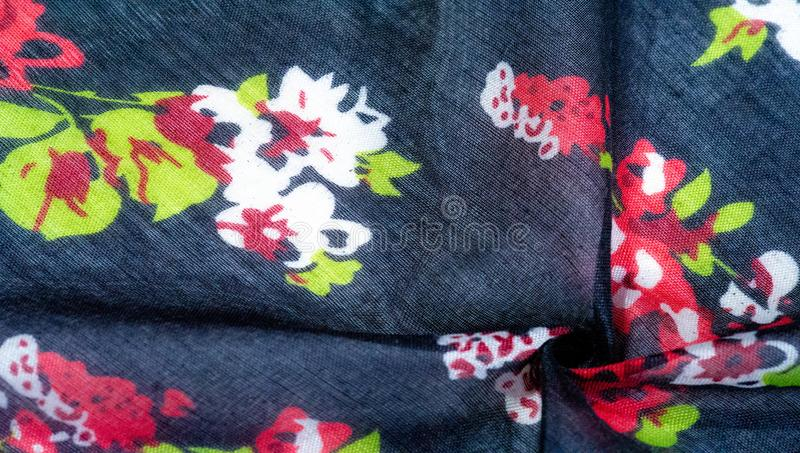 Texture background, dark blue silk fabric with roses painted colors, colors are blue red white green. Red white green royalty free stock photos